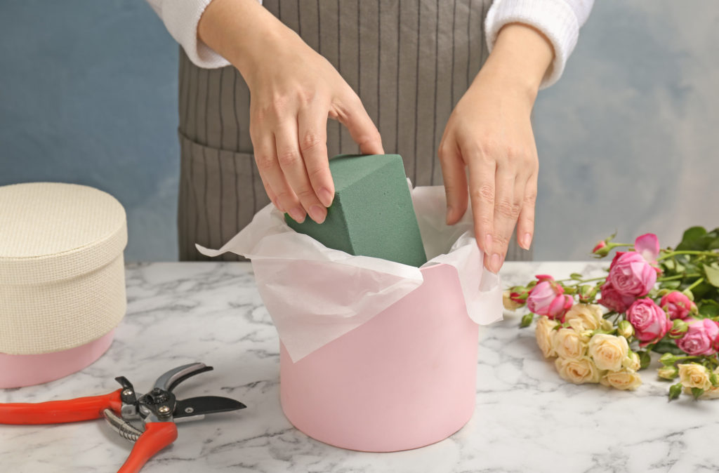 Female florist using floral foam for work at table