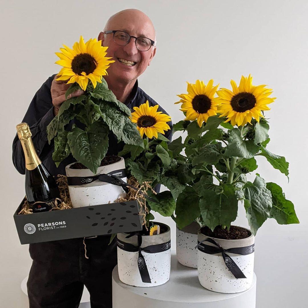 gentleman with sunflower plants