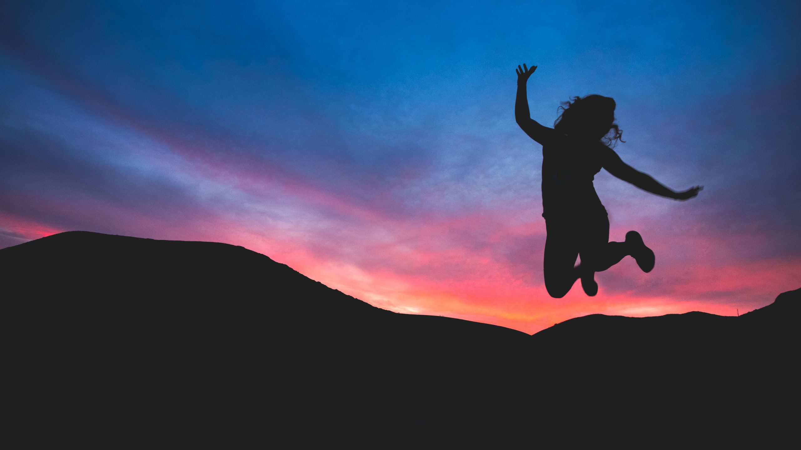 sunset silhouette jumping for joy
